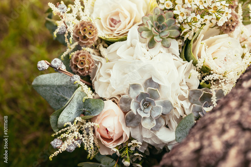 Fényképezés  wedding bouquet with roses and succulents on green grass and woo