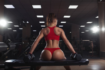 Fototapetasexy young girl resting after dumbbells exercises