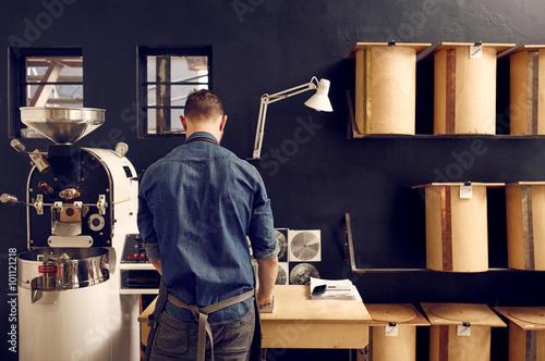 Slika na platnu Man working in his modern coffee roastery with neat storage