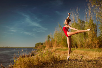 Obraz na PlexiThe young ballerina in a red bathing suit dances on the tips of