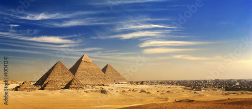 In de dag Egypte Egypt. Cairo - Giza. General view of pyramids and cityscape from the Giza Plateau (on front side: 3 pyramids popularly known as Queens' Pyramids; next: the Pyramid of Mykerinos, Chephren and Cheops)