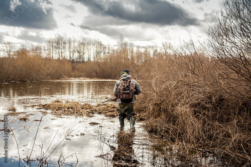 Crédence de cuisine en verre imprimé Chasse hunter man creeping in swamp during hunting period