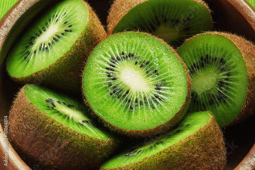 Juicy ripe kiwi fruit in wooden bowl