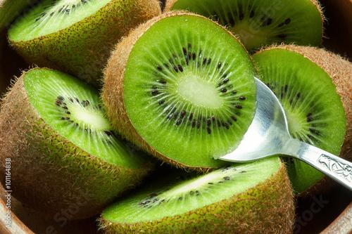 Juicy ripe kiwi fruit in wooden bowl with spoon