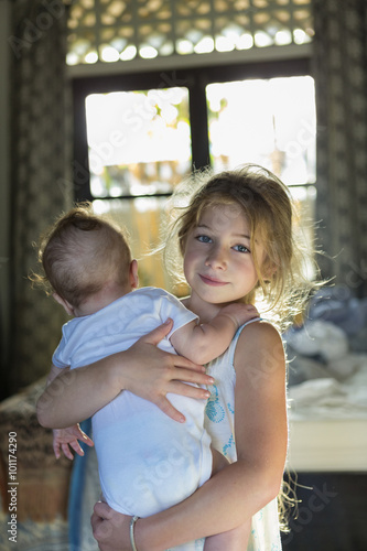 Caucasian girl carrying baby boy in bedroom