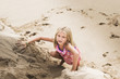 Caucasian girl climbing sand hill on beach