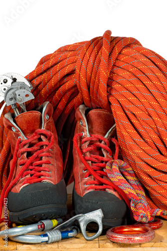 Foto op Plexiglas Alpinisme Climbing Equipment on White Background / Rock climbing equipment with mountaineering boots, climbing cams, descender, carabiners, piton, and a red rope. Isolated on white background
