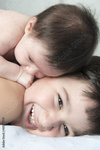Valokuva  Niño jugando con su hermano bebé con un gesto de felicidad en sus caras