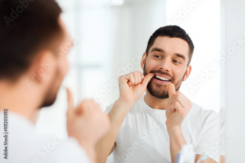 Valokuvatapetti man with dental floss cleaning teeth at bathroom