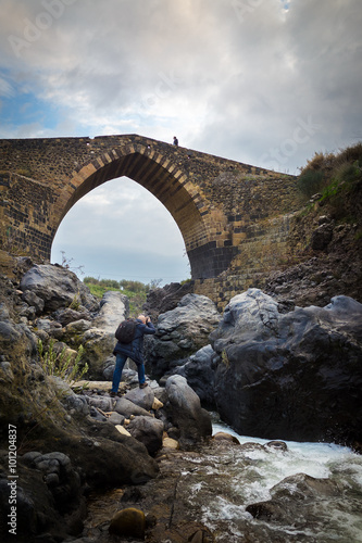 "Valokuva  Photographer taking a photo to a man walking on the ""Bridge of Saracens"": an old"