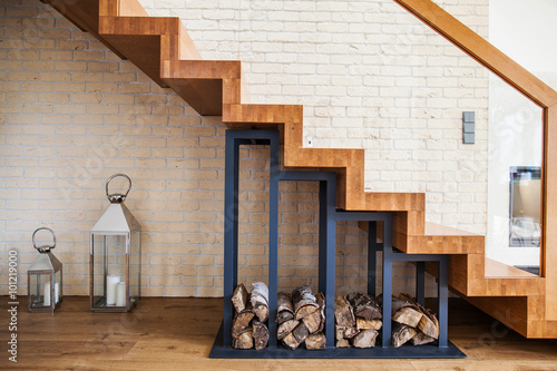 Spoed Foto op Canvas Trappen modern solution to storage pile of wood under the stairs at home