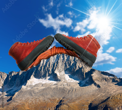 Papiers peints Alpinisme Mountain Climbing Concept / A pair of a mountaineering boots with a red climbing rope on a mountain peak with blue sky and sun rays.