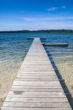 Fototapeta Pomosty - Czyste piękne jezioro i pusty drewniany pomost. Piękna letnia pogoda