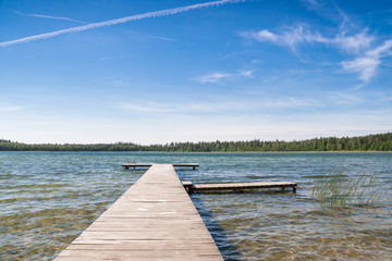 Czyste płytkie jezioro i pusty drewniany pomost. Piękna letnia pogoda