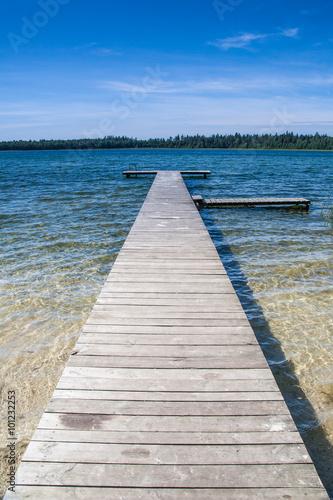 Czyste piękne jezioro i pusty drewniany pomost. Piękna letnia pogoda