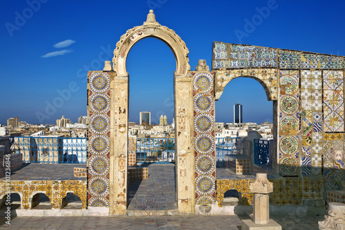 Photo Stands Tunisia Tunisia. Tunis - old town (medina) seen from roof top. Ornamental arches and wall covered tiles with geometric shape motifs