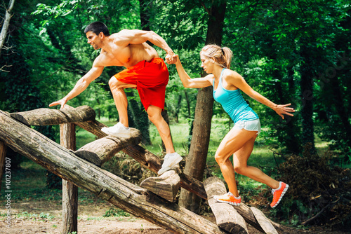 Photo  Couple of athletes crossing fitness trail obstacles