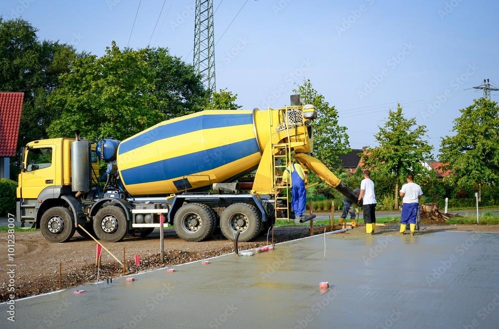Betonmischer liefert Fertigbeton - Bauarbeiter verteilen den Beton ...
