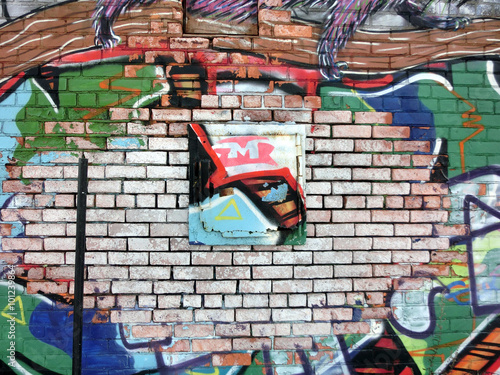 Photo  Colorful brick wall with scraps of paint and graffiti - landscape photo
