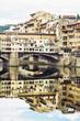 Ponte Vecchio and historic buildings are mirrored in the Arno