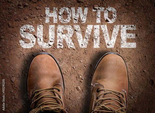 Fototapeta Top View of Boot on the trail with the text: How To Survive