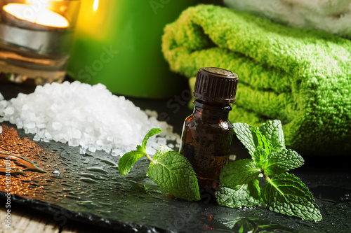 Keuken foto achterwand Spa Peppermint essential oil in a Spa concept with towel, sea salt,