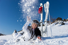 Female Skier Lying On Stomach And Tossing Snow