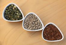 Eatable Seeds (sunflower, Pumpkin, Flax) In Three Bowls Arranged In An Arrow