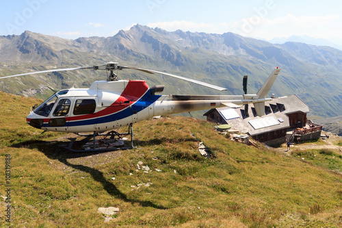Poster Helicopter Transport helicopter landed near alpine hut and mountain panorama in Hohe Tauern Alps, Austria