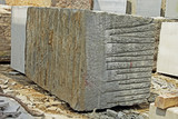 Huge Indian granite blocks stacked for stone processing such as cutting and polishing into flooring slabs for using in building construction.