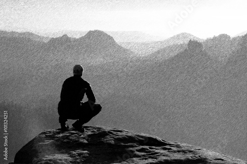 Poster Gris Black and white dashed retro sketch. Moment of loneliness. Man sit on the peak of rock and watching into mist and fog in valley.