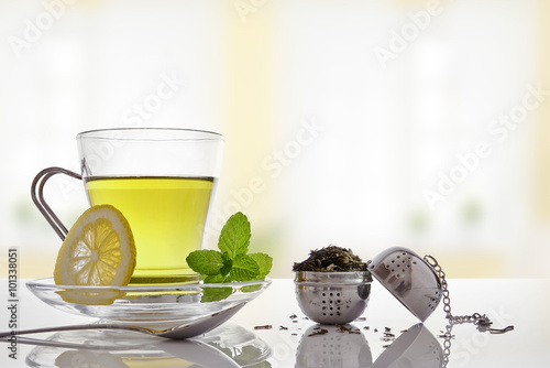 Valokuva  Green tea with mint and lemon with strainer front view