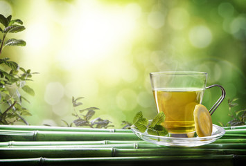 FototapetaOriental green tea with mint and lemon on bamboo front
