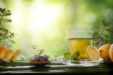 FototapetaOriental green tea with mint and lemons on bamboo front