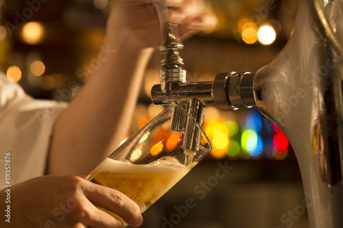 Fotografía  The bartender is pouring draft beer