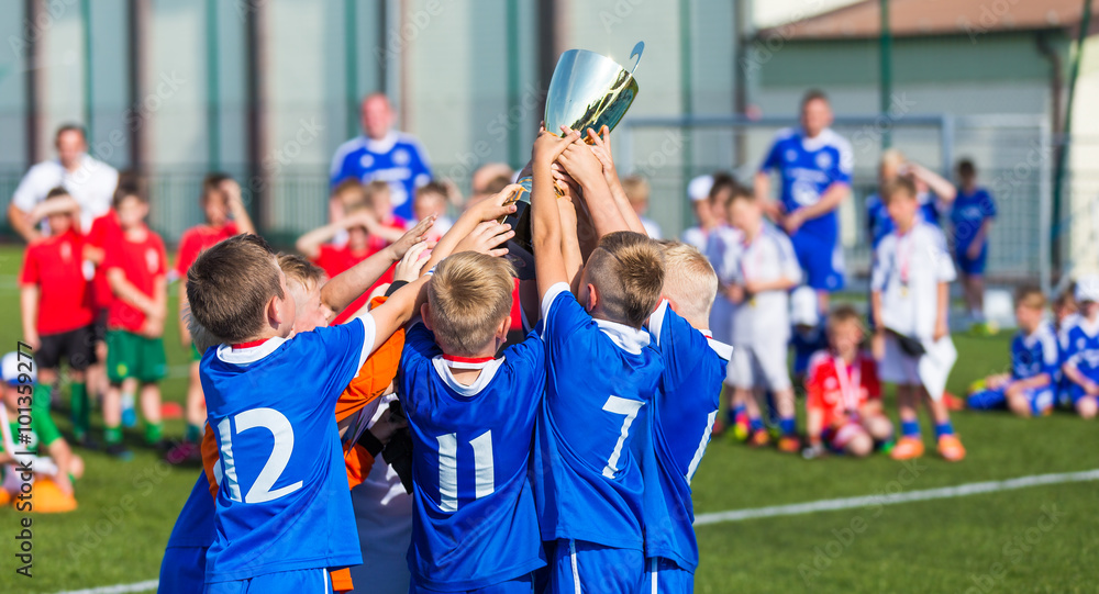 Fototapety, obrazy: Young Sport Team with Trophy. Boys Celebrating Sports Achievement. Young Soccer Players Holding Trophy. Celebrating Soccer Football Championship. Winning team of sport tournament for kids children.
