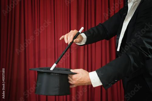 Fotografie, Obraz  Kouzelník s cylindrem a kouzelnou hůlkou předvádění na jevišti