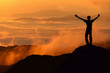 Silhouette of tourist man spread hand on top of a mountain enjoy