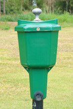The Close-up Golf Ball Washer With Green Golf Course Background.