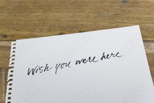 "Photo  ""wish you were here"" hand written on white paper"