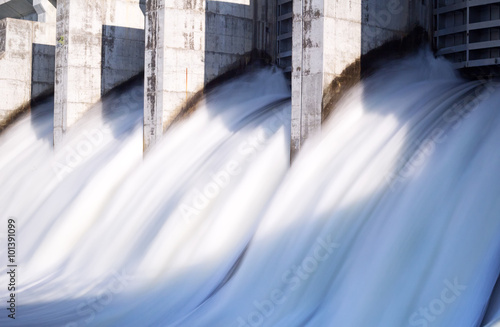 Fotografering Water rushing out of opened gates of a hydro electric power dam in long exposure