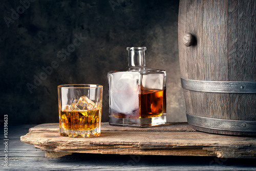 Foto op Aluminium Bar Glass of whiskey with ice decanter and barrel
