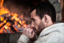 A Man Sitting By The Fireplace