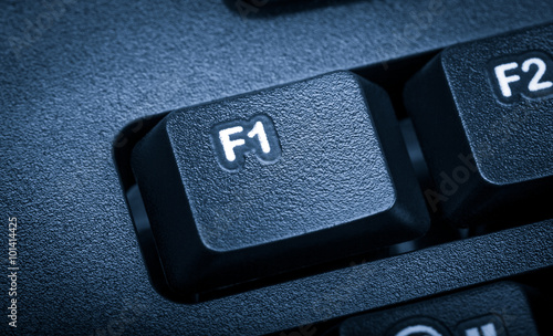 Foto op Canvas F1 Electronic collection - detail black computer keyboard. The focus on F1 key. Toning is blue.