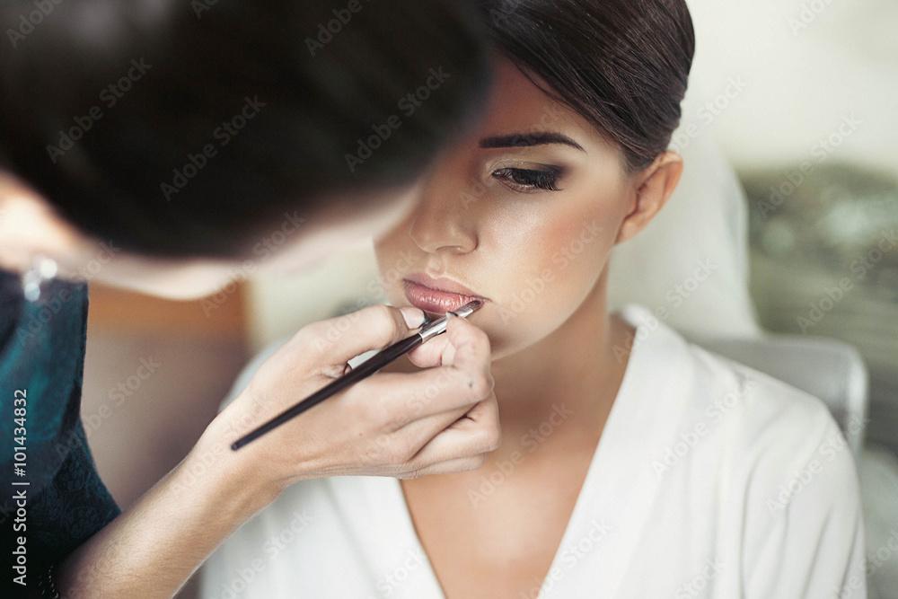 Fototapeta makeup artist makes young beautiful bride bridal makeup