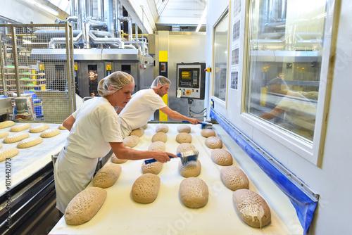 Staande foto Bakkerij Arbeiter in einer Großbäckerei / Fliessband mit Brotlaibern am Backofen