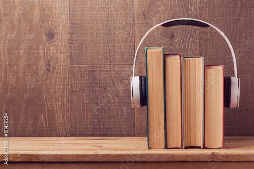 Fotografía  Audio books concept with old books and headphones over wooden background