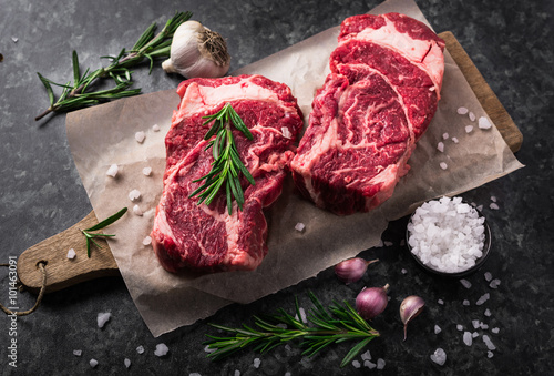 Juliste  Two raw fresh marbled meat black angus steak ribeye, garlic, salt and  on dark b