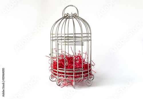 Fotografie, Obraz  Close Steel Bird Cage with Pieces of Red Paper as Nest Isolated on White Backgro