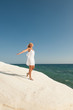 Young woman in white summer dress walking at the seaside